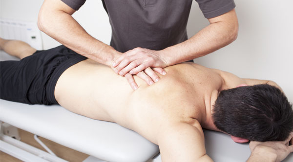 man on table receiving back massage from male masseuse