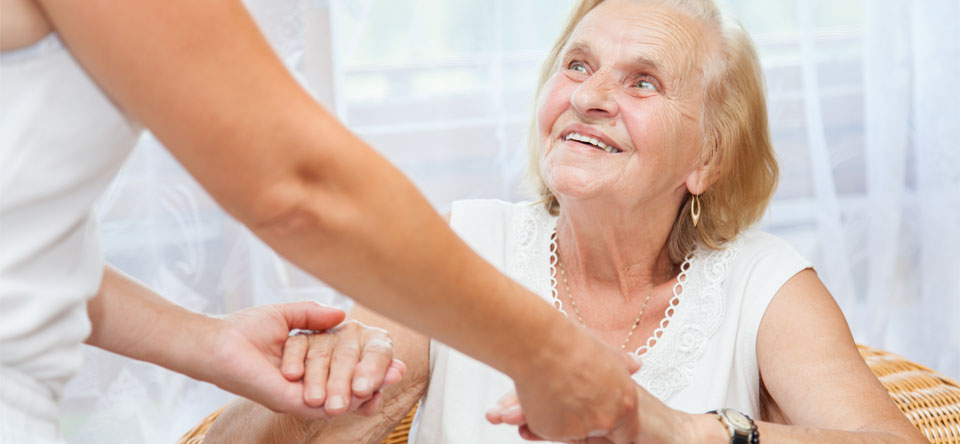 image of woman helping elderly smiling lady
