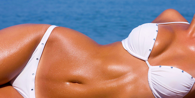 closeup image of woman's stomach laying down in bathing suit on beach